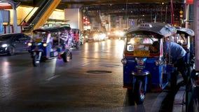 BANGKOK, THAILAND - 18 DECEMBER, 2018: Traditionele Thaise taxi - Tuk Tuk wacht op toeristen langs de weg Nachtverkeer van stock video