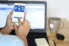Bangkok, Thailand: 17,2019 die mei, Vrouwenhand Samsung-melkweg J7 plus en MAC met de sociale media app gebruikt van Facebook en  royalty-vrije stock foto's
