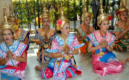Bangkok, Thailand: Erawan Shrine Khong Dancers. Young women in traditional Thai Khong costumes and gilded hats sitting in the prayer position with clasped hands Royalty Free Stock Photography