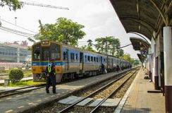 Lifestyle of diverse people travel with Rail transport. BANGKOK, THAILAND - 10 Feb 2018: Diesel railcar at junction Bang Sue train station and Security guard to Stock Image