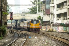 Train is departing from origin bangkok station through commercial building shabby. BANGKOK, THAILAND - 23 Feb 2018 : Train led by locomotive GE is departing Royalty Free Stock Images