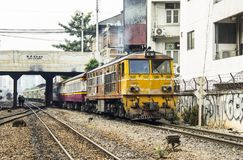 Train is departing from origin bangkok station through commercial building shabby. BANGKOK, THAILAND - 23 Feb 2018 : Train led by old locomotive Alsthom is Stock Photography