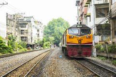 Train through neighborhoods of railroad community. BANGKOK, THAILAND - 23 Feb 2018 : Train To Bangkok Station. through environment have trees and neighborhoods Royalty Free Stock Images