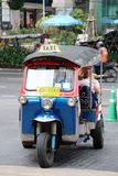 Uk Tuk is a three-wheeled motorized vehicle used as a taxi with passengers on the road at Ploenchit Road. stock photo