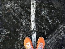 Bangkok, THAILAND - 2. Februar 2018: Orange Schuhe auf den alten Straßen markiert auf nass Asphalt lizenzfreie stockfotos