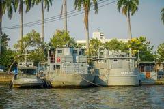 BANGKOK THAILAND - FEBRUARI 09, 2018: Den utomhus- sikten av gråa militära skepp i en flodstrand med något gömma i handflatan trä Royaltyfri Bild
