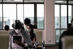 Free Bangkok, Thailand - February 14,2020 : Woman Wearing Mask To Protect Herself From Covid-19 While Using Phone And Sitting In Front Stock Images - 172994404