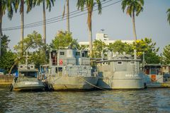 BANGKOK, THAILAND - FEBRUARY 09, 2018: Outdoor beautiful view of gray military ships in a riverside with some palms tree. Behind at yai canal or Khlong Bang stock photo