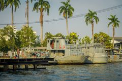 BANGKOK, THAILAND - FEBRUARY 09, 2018: Outdoor view of gray military ships in a riverside with some palms tree behind at. Yai canal or Khlong Bang Luang Tourist royalty free stock photos