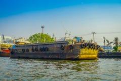 BANGKOK, THAILAND - FEBRUARY 09, 2018: Rusted a old boat at riverside with neumatics hanging, at yai canal or Khlong Royalty Free Stock Photo