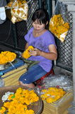 Bangkok, Thailand: Flower Seller. A woman making floral leis using orange Marigolds to sell to passerby while sitting on a small stool on Thanon Charoen Krung Royalty Free Stock Photography
