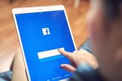 Bangkok Thailand - Januari 9, 2018: handen trycker på den Facebook skärmen på pro-äppleipad, socialt massmedia använder Royaltyfri Fotografi