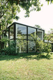 BANGKOK, THAILAND - JANUARY 22, 2017: A glass house near green t Royalty Free Stock Images