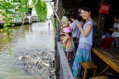 Bangkok, Thailand : Japanese tourists are feeding fish  Royalty Free Stock Photos