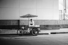 Bangkok, Thailand - 17. Juli 2016: Verkäuferwartung des alten Mannes einen Kunden auf einer Straße in Bangkok, Thailand, Schwarzw Lizenzfreie Stockfotografie