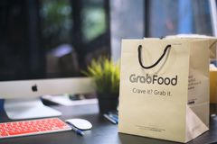 "BANGKOK,THAILAND -JULY 7, 2019: ""GRAB FOOD"" paper bag on wooden table at home office ,Food delivery service through its mobile. Application.food royalty free stock photography"