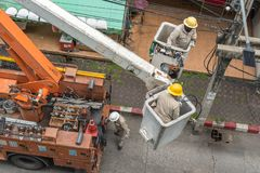 Electricians in uniform on aerial work platform. Bangkok, Thailand - July 22, 2018: electricians in uniform repair an electric pole being on aerial work stock photography