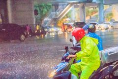 Bangkok, Thailand - July 6. 2017: People wear helmet and raincoat ride motorbike in heavy rain through the water on street during royalty free stock photos