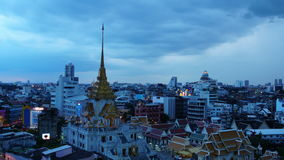 BANGKOK, THAILAND - JULY 23, 2017 : Time-lapse day to night Bangkok cityscape Local buildings and Wat Traimit at twilight evening. Time-lapse day to night stock video footage