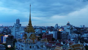 BANGKOK, THAILAND - JULY 23, 2017 : Time-lapse day to night Bangkok cityscape Local buildings and Wat Traimit at twilight evening. Time-lapse day to night stock footage