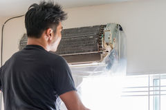 Cleaning air conditioner by water for clean a dust Stock Photo