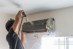 Cleaning air conditioner by water for clean a dust Royalty Free Stock Photos