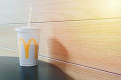 Free Bangkok, Thailand - June, 01 2019 : McDonalds Takeaway Cola Plastic Cup On Wood Table In Shopping Mall With Orange Leak Light And Royalty Free Stock Photos - 156583358