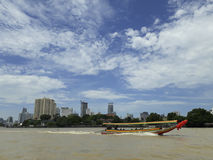 BANGKOK, THAILAND - June 13, 2017: Boats and buildings on the Ch. Ao Phraya River in the blue sky in Bangkok, Thailand Stock Photos