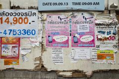 Bangkok, Thailand - June 29, 2015: Messy and dirty advertisement papers on old wooden wall in Bangkok street Stock Images