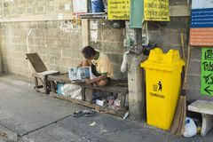 Bangkok, Thailand - June 29, 2015: Old man reading newspaper on old wooden bench, next to rubbish bin, on small alley in Bangkok.  Royalty Free Stock Images
