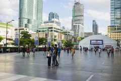 Bangkok, Thailand - June 29, 2015: People walking on spacious sidewalk in front of Central World building, Bangkok. High buildings. On background Royalty Free Stock Photo