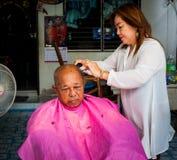 BANGKOK THAILAND - JUNE 3, 2016 : Woman barber haircut to The Ol. D man in Bangkok Thailand Royalty Free Stock Photography