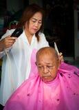 BANGKOK THAILAND - JUNE 3, 2016 : Woman barber haircut to The Ol. D man in Bangkok Thailand Royalty Free Stock Photo