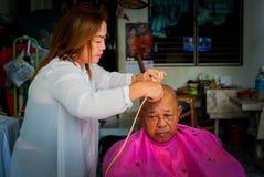 BANGKOK THAILAND - JUNE 3, 2016 : Woman barber haircut to The Ol. D man in Bangkok Thailand Royalty Free Stock Photos