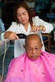 BANGKOK THAILAND - JUNE 3, 2016 : Woman barber haircut to The Ol. D man in Bangkok Thailand Stock Photos