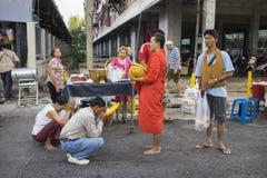 Bangkok, Thailand - Juni 28, 2015: Mensen die eerbied bidden aan monnik op de straat van Bangkok Ruwweg 95 percent van de Thaise  Royalty-vrije Stock Foto