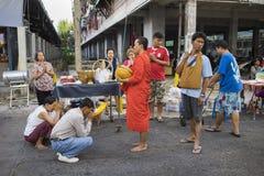 Bangkok, Thailand - Juni 28, 2015: Mensen die eerbied bidden aan monnik op de straat van Bangkok Ruwweg 95 percent van de Thaise  Stock Fotografie