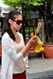 Bangkok Thailand: Kvinna som ber på den Erawan relikskrinen Arkivfoto