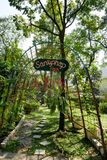 BANGKOK, THAILAND - 11. MÄRZ 2017: Eine Wegweise und ein grüner Wald Lizenzfreie Stockfotografie