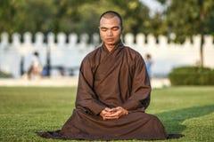 Bangkok, Thailand, am 4. März 2016: Junger Mönch, der im Park, sitzend auf einem Gras meditiert Lizenzfreies Stockbild