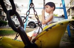 BANGKOK, THAILAND - MAART 24: De niet geïdentificeerde jongen zit op een schommeling die door kettingen in de speelplaats van het stock fotografie