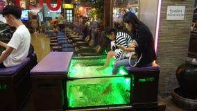 Bangkok, Thailand - 3. Mai 2018: Eine Dame ist in einem Badekurortfisch an Yaowarat-Straße in Bangkok-` s Chinatown Bezirk stock video footage