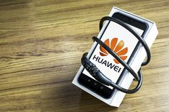 Bangkok Thailand - Maj 23, 2019: Huawei telefoner med avkodare p? konstgjord tr?durk i hemmet, Huawei s?kerhetsproblem, buss royaltyfri illustrationer