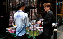Bangkok, Thailand: Man Buying DVD Videos. Western business man buying bargain DVD videos from a street vendor on Silom Road in Bangkok, Thailand Stock Images
