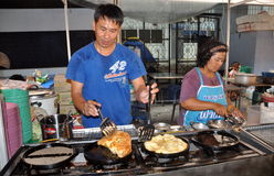 Bangkok, Thailand: Man Cooking Omelettes. Thai man dripping with perspiration makes a fluffy egg omelette on a four-burner grill at the MBK outdoor food market Royalty Free Stock Images
