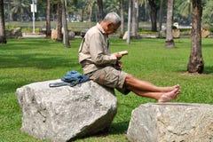 Bangkok, Thailand: Man Reading in Lumphini Park Stock Photos