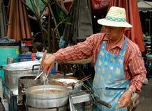 Bangkok, Thailand: Mann, der Nahrung auf Straße kocht Lizenzfreie Stockfotos