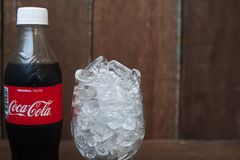 BANGKOK, THAILAND-MARCH 2, 2018 : Close up Coca-Cola bottle with. Ice in glass on vintage style background stock images