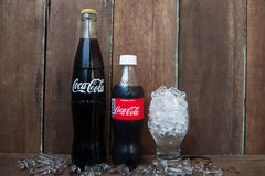 BANGKOK, THAILAND-MARCH 2, 2018 : Close up Coca-Cola bottle with. Ice in glass on vintage style background stock photo