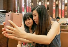 BANGKOK, THAILAND - MARCH 10: Unidentified pair of mother and daughter taking a selfie with a smartphone in Yayoi restaurant in stock photo